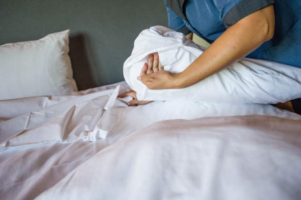 A housekeeper makes a bed at Aspen Square Condominium Hotel. General Manager Warren Klug says few Anglos apply for the jobs.