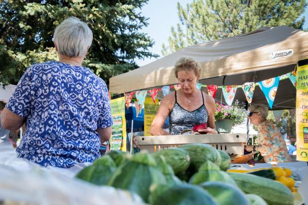 Glenwood Springs resident Cindy Lundin makes a purchase from the Early Morning Orchards stand at the Downtown Market on Tuesday evening.