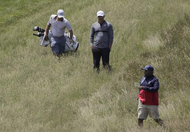 Brooks Koepka, center, lines up a shot from the rough along the 9th fairway during a practice round for the U.S. Open Golf Championship, Monday, June 11, 2018, in Southampton, N.Y. (AP Photo/Julie Jacobson)