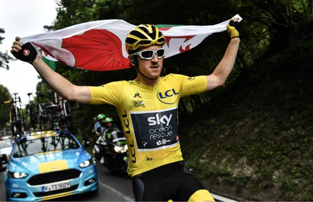 Britain's Geraint Thomas, wearing the overall leader's yellow jersey, holds the flag of Wales during the 21st and last stage of the 105th edition of the Tour de France cycling race between Houilles and Paris Champs-Elysees, Sunday, July 29, 2018. (Marco Bertorello, Pool via AP)