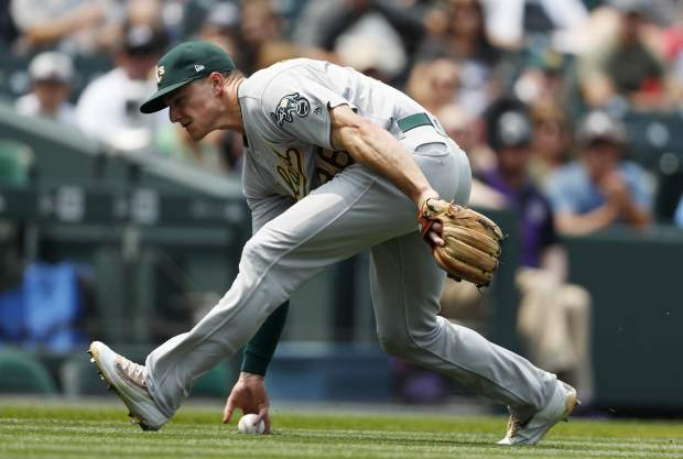 Oakland Athletics third baseman Matt Chapman tries to pick up a bunt-single off the bat of Colorado Rockies' Charlie Blackmon in the first inning of a baseball game Sunday, July 29, 2018, in Denver. (AP Photo/David Zalubowski)