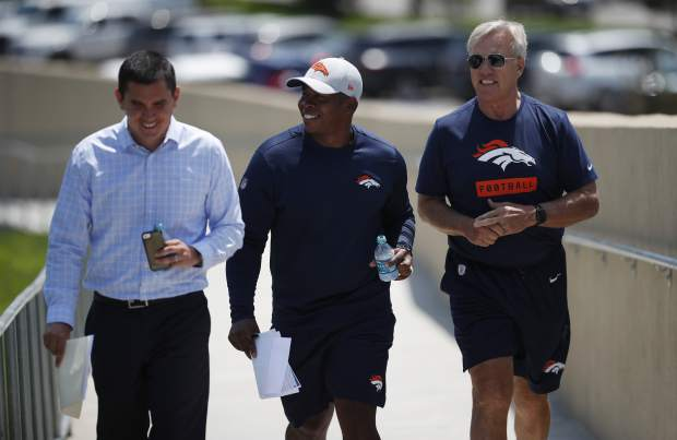 Denver Broncos general manager John Elway, right, and head coach Vance Joseph, center, joke with Patrick Smyth, executive vice president of public and community relations, as they head to a news conference as players report to training camp Friday, July 27, 2018, at the team's headquarters in Englewood, Colo. (AP Photo/David Zalubowski)
