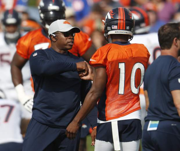 Denver Broncos head coach Vance Joseph, left, greets wide receiver Emmanuel Sanders at the team's NFL football training camp Saturday, July 28, 2018, in Englewood, Colo. (AP Photo/David Zalubowski)