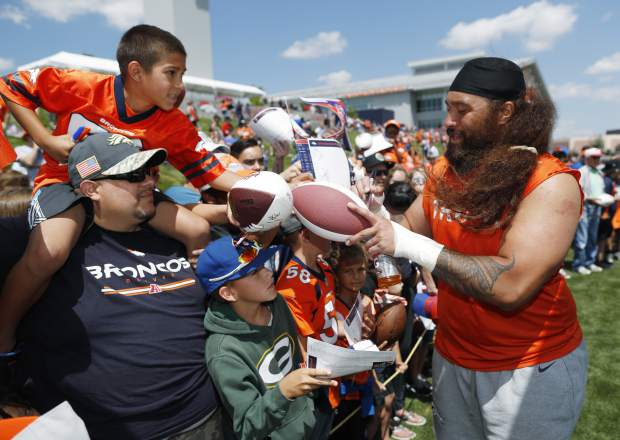 Denver Broncos defensive tackle Domata Peko Sr. signs autographs for fans after drills at the team's NFL football training camp Monday, July 30, 2018, in Englewood, Colo. (AP Photo/David Zalubowski)