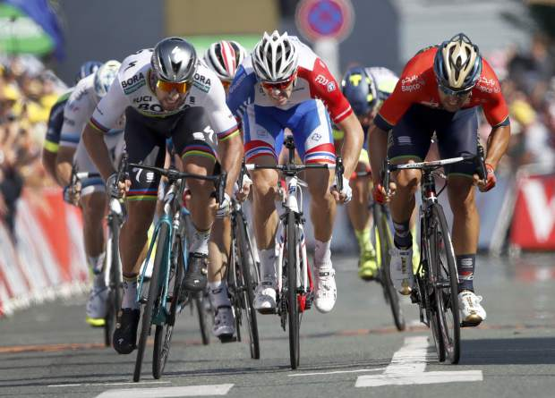 Slovakia's Peter Sagan, left, Italy's Sonny Colbrelli, right, and France's Arnaud Demare sprint to the finish line during the finish line to win the second stage of the Tour de France cycling race over 182.5 kilometers (113.4 miles) with start in Mouilleron-Saint-Germain and finish in La Roche Sur-Yon, France, Sunday, July 8, 2018. Sagan won the stage. (AP Photo/Christophe Ena )