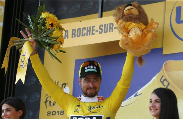 Stage winner Slovakia's Peter Sagan, wearing the overall leader's yellow jersey, celebrates on the podium after the second stage of the Tour de France.