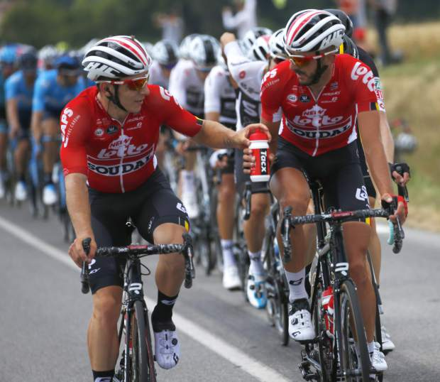 In this Saturday, July 14, 2018, image, Belgium's Jelle Vanendert, right, hands water bottles to Belgium's Jasper De Buyst during the eight stage of the Tour de France cycling race over 181 kilometers (112.5 miles) with start in Dreux and finish in Amiens, France, Saturday, July 14, 2018. Certain riders in cycling are called a