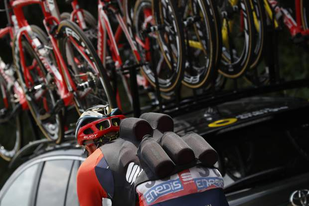 In this Friday, July 13, 2018, image, Italy's Marco Marcato carries water bottles for his teammates during the seventh stage of the Tour de France cycling race over 231 kilometers (143.5 miles) with start in Fougeres and finish in Chartres, France, France. Certain riders in cycling are called a