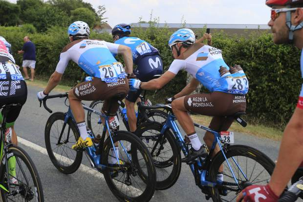 In this Saturday, July 14, 2018, image, France's Alexis Vuillermoz, right, hands water bottles to France's Pierre Roger Latour, left, during the eight stage of the Tour de France cycling race over 181 kilometers (112.5 miles) with start in Dreux and finish in Amiens, France. Certain riders in cycling are called a