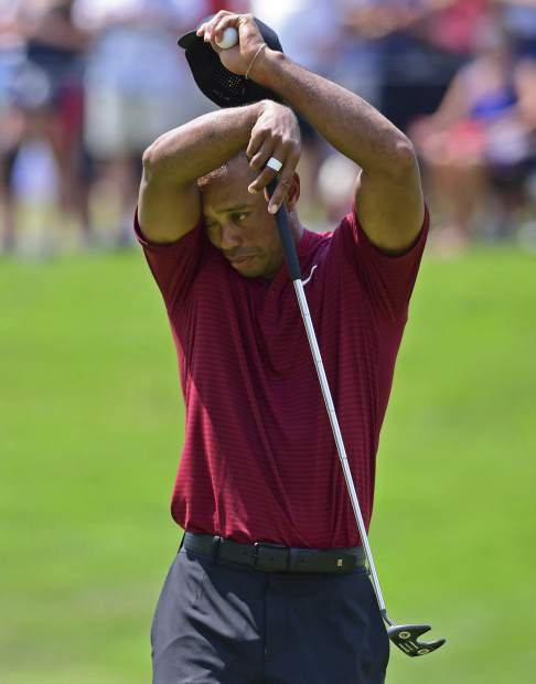 Tiger Woods wipes his face on the seventh hole during the final round of the Bridgestone Invitational golf tournament at Firestone Country Club, Sunday, Aug. 5, 2018, in Akron, Ohio. (AP Photo/David Dermer)