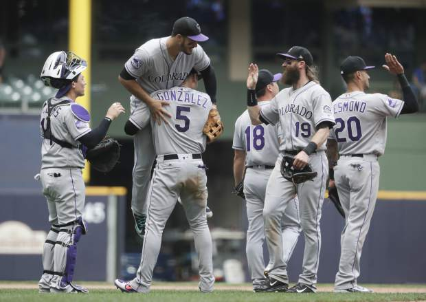 Colorado Rockies' Carlos Gonzalez (5) lots Nolan Arenado after the 11th inning of a baseball game against the Milwaukee Brewers Sunday, Aug. 5, 2018, in Milwaukee. The Rockies won 5-4. (AP Photo/Morry Gash)