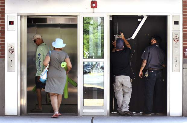 A couple heads for a relaxing day at the Glenwood Hot Springs as Dan Smith and Jason Garcia, with Thyssenkrupp Elevators out of Denver, service and evaluate one of the elevators at the Seventh Street Station Thursday in Glenwood Springs.