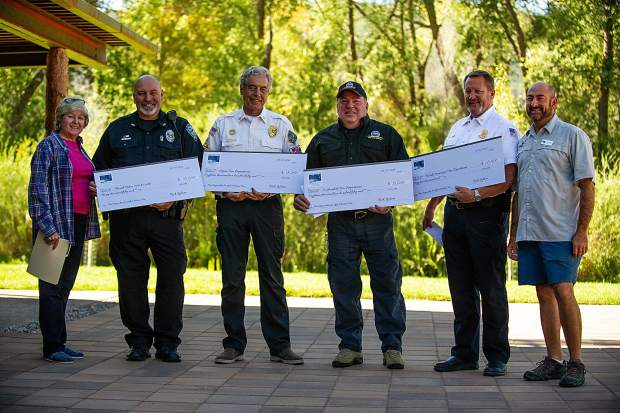 First responders to the Lake Christine Fire are presented cardboard checks Thursday from the Roaring Fork Conservancy. Left to right are Sarah Woods of the conservancy, Basalt Police Chief Greg Knott, Aspen Fire Chief Rick Balentine, Carbondale Fire Chief Rob Goodwin, Basalt-Snowmass Village Fire Chief Scott Thompson and Conservancy Executive Director Rick Lofaro.