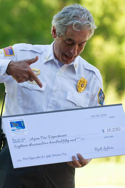 Aspen Fire Chief Rick Balentine points to a replica check for $18,250 the Aspen Volunteer Fire Department received for aiding in fighting the Lake Christine Fire.