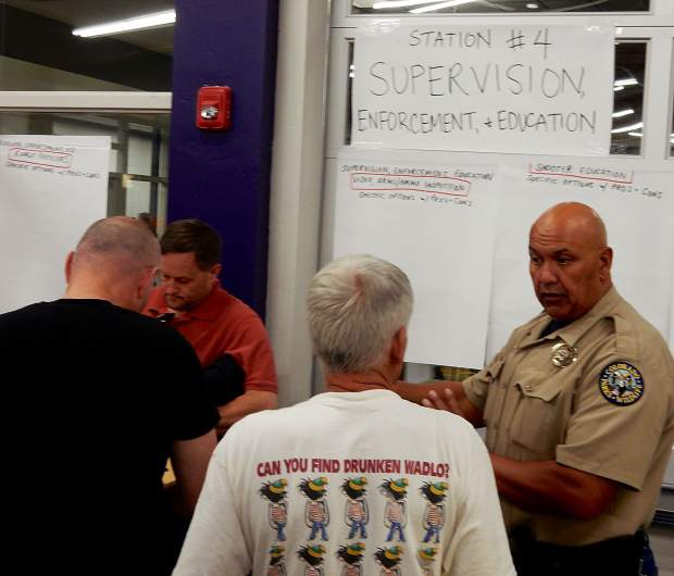 A Colorado Parks and Wildlife officer talks with attendees of a meeting Monday at Basalt High School. The public was urged to offer written comments on eight issues at the gun range, including station number 4 on supervision.