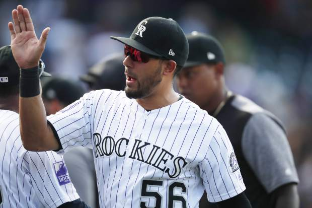 Colorado Rockies' Noel Cuevas is congratulated by teammates after the ninth inning of a baseball game against the San Francisco Giants, Monday, Sept. 3, 2018, in Denver. The Rockies won on a pinch-hit single by Cuevas that brought in the tying and go-ahead runs. (AP Photo/David Zalubowski)
