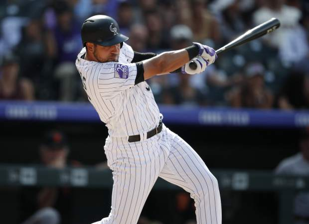 Colorado Rockies pinch-hitter Noel Cuevas follows through with his swing after connecting for a single to drive in the tying and go-ahead runs off San Francisco Giants relief pitcher Tony Watson in the eighth inning Monday in Denver.