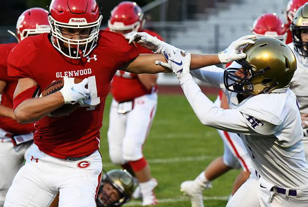 Glenwood Springs Demon stiff-arms the defending Holy Family Tiger during Friday night's game at Stubler Memorial Field.