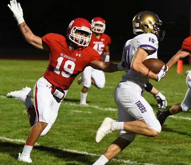 Glenwood Springs Demon Miguel Herrera attempts to stop Holy Family Tiger Braeden Peters during Friday night's game at Stubler Memorial Field.