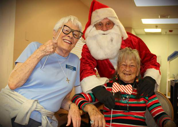 Betty Bendetti, with the striped tie, helping at a Rifle Veterans Home holiday event.