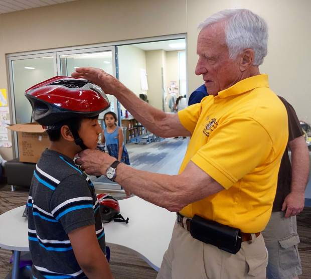 Karl Oelke fits a youngster with a new bike helmet as part of a Glenwood Springs Kiwanis Club project.