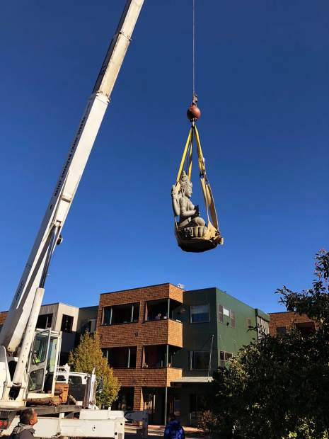 A crane lifts and carries a carving of the goddess Lakshmi from Bali and places it at True Nature Healing Arts in Carbondale on the morning of Monday, Oct. 15.