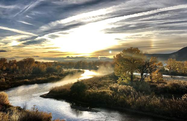 The sun rises above the Colorado River valley near Rifle Tuesday, illuminating the final hints of fall clinging to the trees along the banks.