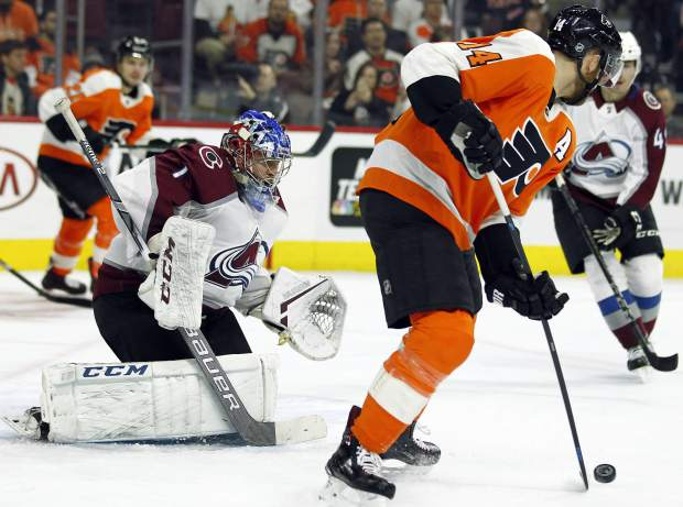 Colorado Avalanche goalie Semyon Varlamov, left, defends the goal as Philadelphia Flyers' Sean Couturier tries to control the puck Wayne Simmonds during the second period of an NHL hockey game, Monday, Oct. 22, 2018, in Philadelphia. (AP Photo/Tom Mihalek)