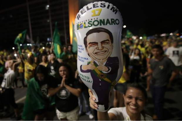 A supporter holds a balloon with the image of presidential candidate Jair Bolsonaro, during celebration in front of the National Congress, in Brasilia, Brazil, Sunday, Oct. 28, 2018. Brazil's Supreme Electoral Tribunal declared the far-right congressman the next president of Latin America's biggest country. (AP Photo/Eraldo Peres)