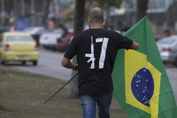 A man, wearing a T-shirt with the voting number 17 associated with President-elect Jair Bolsonaro, walks with a Brazilian national flag in Rio de Janeiro, Brazil, Monday, Oct. 29, 2018. In some of his first words to the nation as president-elect, Bolsonaro has promised to defend the constitution and unite a bitterly divided populace. (AP Photo/Leo Correa)