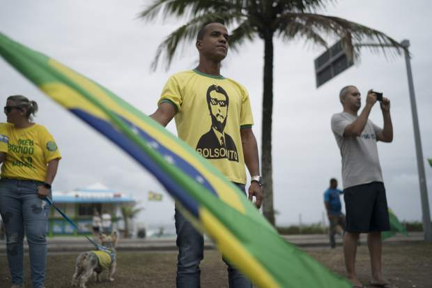 Supporters of President-elect Jair Bolsonaro gather in front of his residence in Rio de Janeiro, Brazil, Monday, Oct. 29, 2018. Bolsonaro's victory moved Brazil, the world's fourth-largest democracy, sharply to the right after four consecutive elections in which candidates from the left-leaning Workers' Party won. (AP Photo/Leo Correa)
