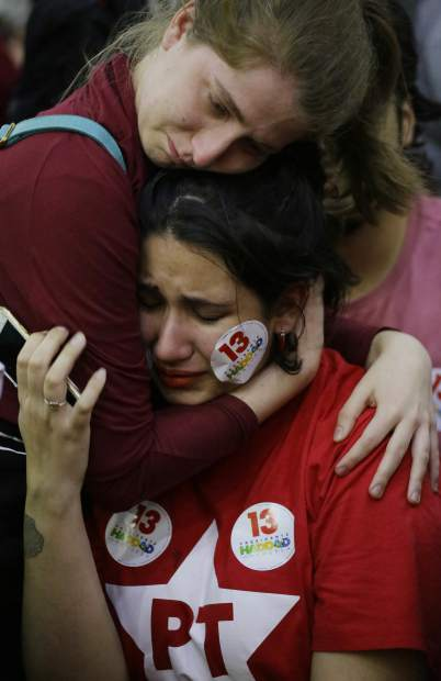 A supporter of Workers' Party presidential candidate Fernando Haddad embraces a fellow distraught supporter, after learning that rival Jair Bolsonaro was declared the winner in the presidential runoff election, in Sao Paulo, Brazil, Sunday, Oct. 28, 2018. Addressing supporters in Sao Paulo, Haddad did not concede or even mention Bolsonaro by name. Instead, his speech was a promise to resist. (AP Photo/Nelson Antoine)