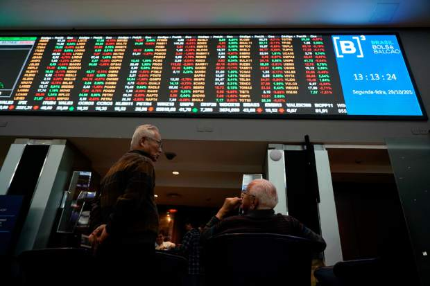 Two men talk underneath a display of Brazil's Bovespa index at Sao Paulo's Stock Exchange, Monday, Oct. 29, 2018. The Bovespa index rose in morning trading after far-right politician Jair Bolsonaro was elected president, but it later turned lower and fell 2,24 percent. Stocks climbed earlier this month after Bolsonaro led the previous round of voting, as investors preferred him to leftist parties. (AP Photo/Victor R. Caivano)