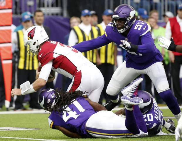 FILE - In this Oct. 14, 2018, file photo, Arizona Cardinals quarterback Josh Rosen, left, is sacked by Minnesota Vikings defenders Anthony Harris (41), Mackensie Alexander (20) and Stephen Weatherly (91) during the first half of an NFL football game, in Minneapolis. The Arizona Cardinals can't run the ball, the Denver Broncos can't stop the run. The ground game could be the deciding factor when the two struggling teams meet Thursday night, Oct. 18.(AP Photo/Bruce Kluckhohn, File)