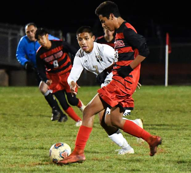 Glenwood Springs Demon Justin Garces dribbles the ball past the defending Battle Mountain Huskies during Tuesday night's game at Stubler Memorial Field.