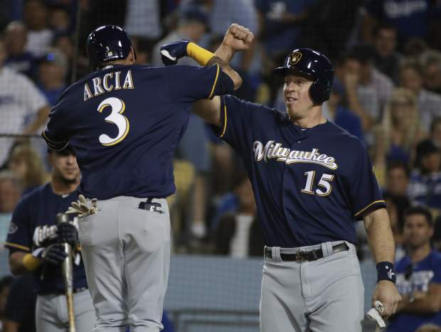 Milwaukee Brewers' Orlando Arcia celebrates his two-run home run with Erik Kratz (15) during the seventh inning of Game 3 of the National League Championship Series baseball game against the Los Angeles Dodgers Monday, Oct. 15, 2018, in Los Angeles. (AP Photo/Jae Hong)