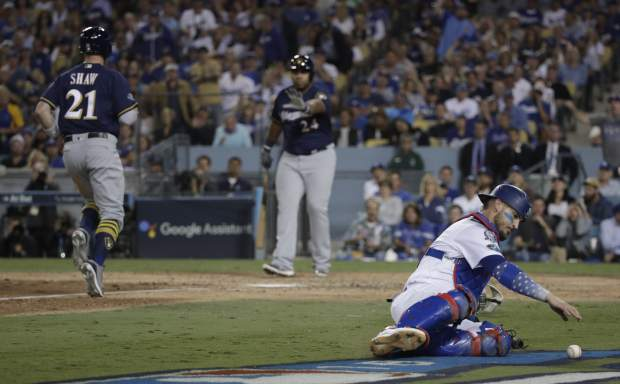 Los Angeles Dodgers catcher Yasmani Grandal goes after a wild pitch as Milwaukee Brewers' Travis Shaw scores during the sixth inning of Game 3 of the National League Championship Series baseball game Monday, Oct. 15, 2018, in Los Angeles. (AP Photo/Jae Hong)