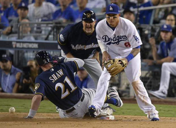 Milwaukee Brewers' Travis Shaw slides into third after hitting a triple during the sixth inning of Game 3 of the National League Championship Series baseball game against the Los Angeles Dodgers Monday, Oct. 15, 2018, in Los Angeles. (AP Photo/Mark J. Terrill)