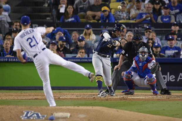 Milwaukee Brewers' Travis Shaw hits a triple during the sixth inning of Game 3 of the National League Championship Series baseball game against the Los Angeles Dodgers Monday, Oct. 15, 2018, in Los Angeles. (AP Photo/Mark J. Terrill)