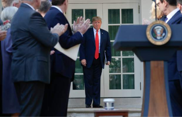 President Donald Trump is applauded as he walks out of the Oval Office to announce a revamped North American free trade deal, in the Rose Garden of the White House in Washington, Monday, Oct. 1, 2018. The new deal, reached just before a midnight deadline imposed by the U.S., will be called the United States-Mexico-Canada Agreement, or USMCA. It replaces the 24-year-old North American Free Trade Agreement, which President Donald Trump had called a job-killing disaster. (AP Photo/Pablo Martinez Monsivais)