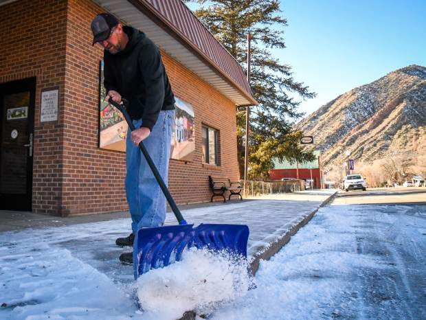 Town of New Castle employee Jeremy Heiser shovels snow and ice off the sidewalk in front of the New Castle Community Center on Monday afternoon.