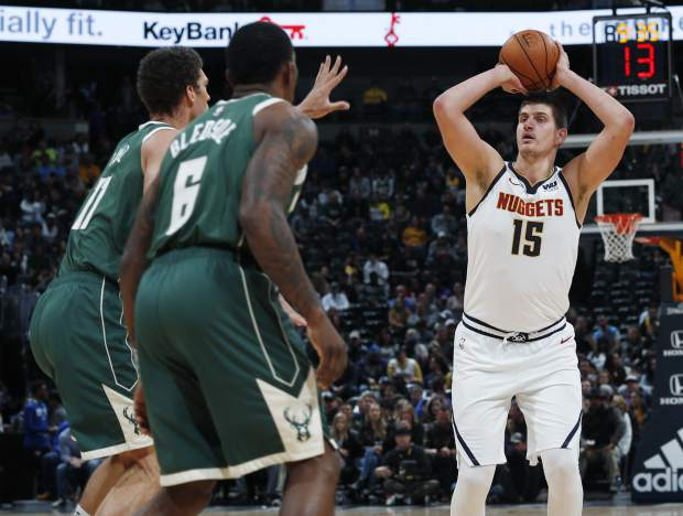 Denver Nuggets center Nikola Jokic, right, shoots for the rim over Milwaukee Bucks guard Eric Bledsoe, front left, and center Brook Lopez in the first half of an NBA basketball game Sunday, Nov. 11, 2018, in Denver. (AP Photo/David Zalubowski)