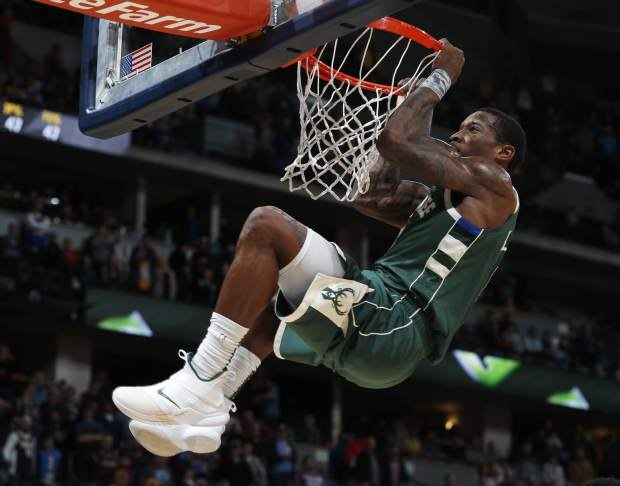 Milwaukee Bucks guard Eric Bledsoe hangs from the rim after dunking the ball for a basket late in the second half of an NBA basketball game against the Denver Nuggets Sunday, Nov. 11, 2018, in Denver. Milwaukee won 121-114. (AP Photo/David Zalubowski)