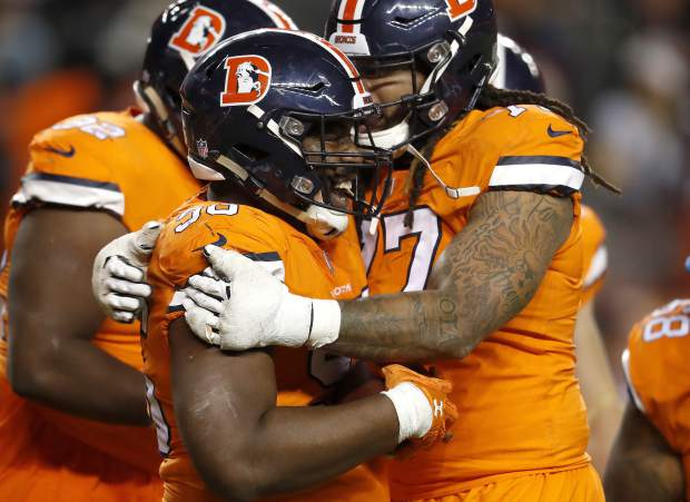 Denver Broncos defensive end Shelby Harris (96) celebrates his interception in the end zone with offensive tackle Billy Turner during the second half of an NFL football game against the Pittsburgh Steelers, Sunday, Nov. 25, 2018, in Denver. The Broncos won 24-17. (AP Photo/David Zalubowski)