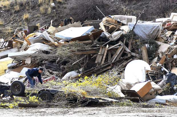 A customer drops tree branches off in the wood pile at the South Canyon Landfill Friday.