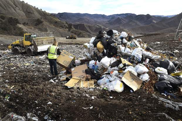 In this November 2018 photo, Parker Jones, a landfill operator at South Canyon Landfill, waits for the bulldozer to push a load of trash into the pit.