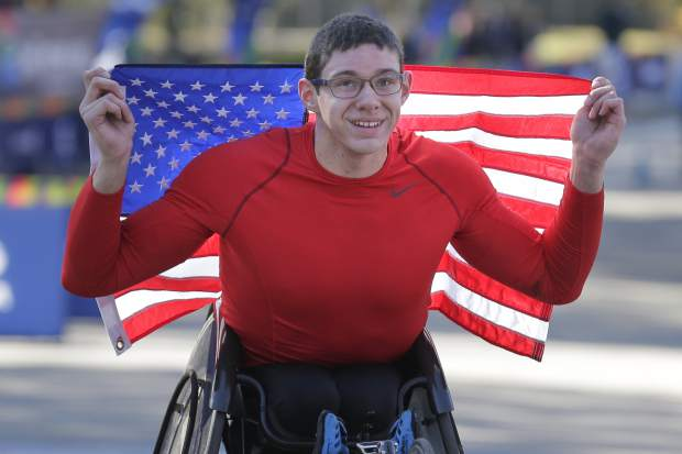 Daniel Romanchuk of the United States poses for a picture after crossing the finish line first in the men's wheelchair division of the New York City Marathon in New York, Sunday, Nov. 4, 2018. (AP Photo/Seth Wenig)