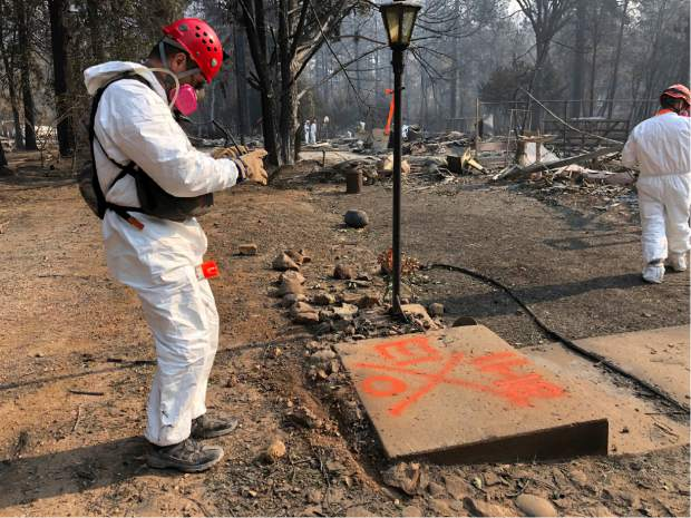 A volunteer member of an El Dorado County search and rescue team photographs the orange spray paint that marks the ruins of a home to show that no human remains were found at the location in Paradise, Calif., Sunday, Nov. 18, 2018, following a Northern California wildfire. (AP Photo/Sudhin Thanawala)