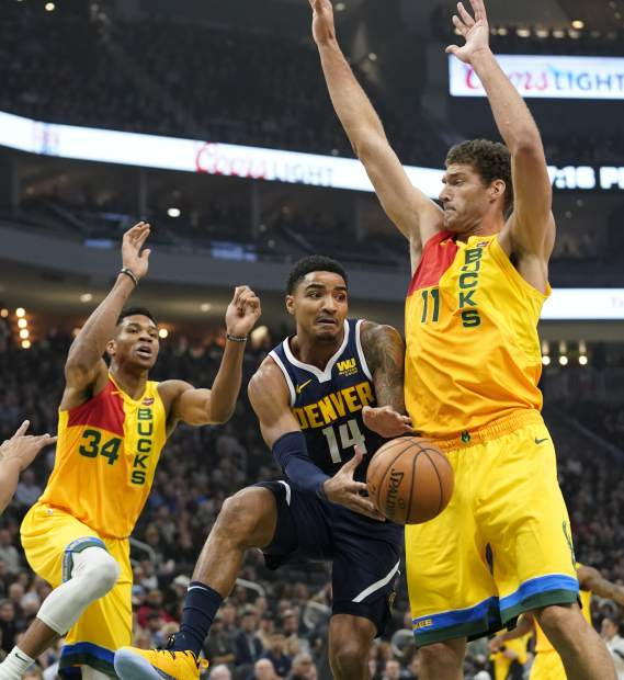 Denver Nuggets' Gary Harris passes around Milwaukee Bucks' Brook Lopez and Giannis Antetokounmpo during the first half of an NBA basketball game Monday, Nov. 19, 2018, in Milwaukee. (AP Photo/Morry Gash)