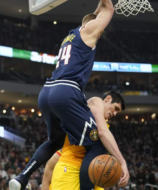 Denver Nuggets' Mason Plumlee dunks over Milwaukee Bucks' Ersan Ilyasova during the first half of an NBA basketball game Monday, Nov. 19, 2018, in Milwaukee. (AP Photo/Morry Gash)